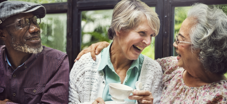 An older man and two older women laughing over a cup of tea