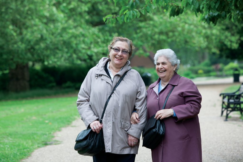 Park Walks: two older people smiling while walking in the park.