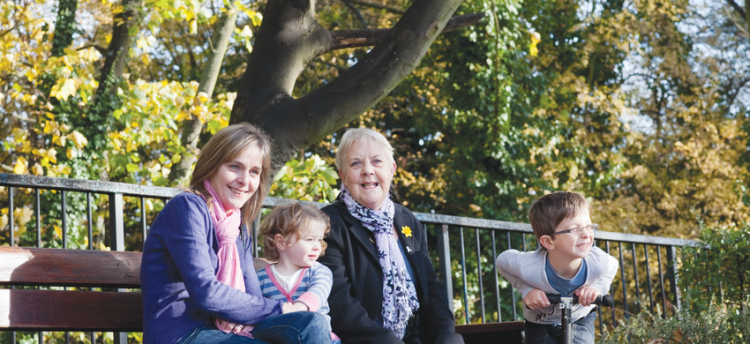 A grandmother, her daughter and grandchildren sat on a park bench together smiling. Sandwich Generation