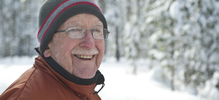 An older person in the cold weather surrounded by snow.